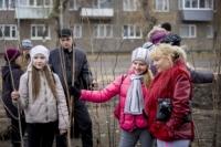 Школьники и взрослые участвуют в посадке деревьев.