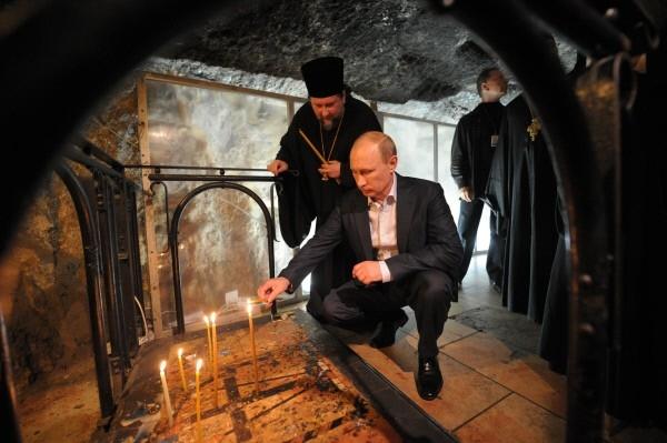 Президент России Владимир Путин ставит свечу во время посещения Храма Гроба Господня в Иерусалиме.