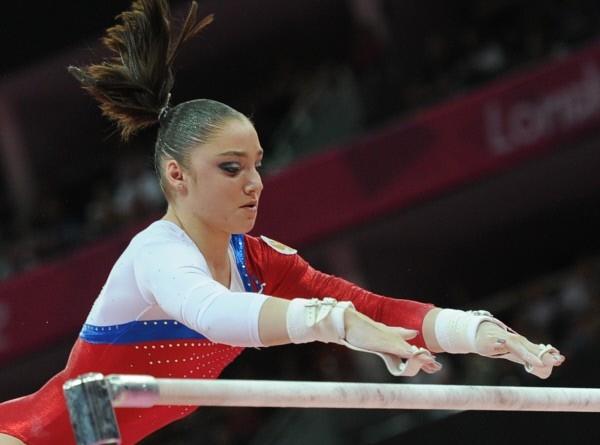 Россиянка Алия Мустафина, занявшая первое место, выполняет упражнения на брусьях во время финальных соревнований по спортивной гимнастике среди женщин на ХХХ Олимпийских играх 2012 года в Лондоне.