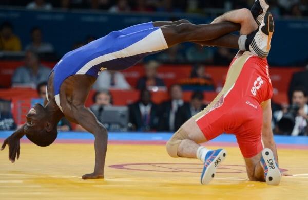 Борцы Джамал Отарсултанов (Россия) и Наателе Сему Шилимела (Намибия) (справа налево) во время поединка 1/8 финала на соревнованиях по вольной борьбе среди мужчин в весовой категории до 55 кг на Олимпийских играх 2012 года в Лондоне.