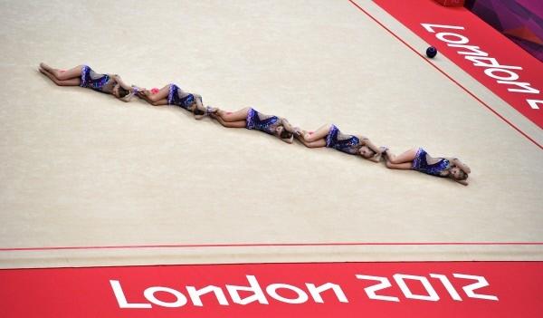 Канадские гимнастки выполняют упражнения с мячом во время квалификации в групповых соревнованиях по художественной гимнастике на ХХХ летних Олимпийских играх 2012 года в Лондоне.