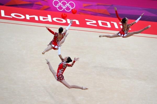 Украинские гимнастки выполняют упражнения с мячом во время квалификации в групповых соревнованиях по художественной гимнастике на ХХХ летних Олимпийских играх 2012 года в Лондоне.