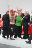Когда лидеры государства осматривали стенд Volksvagen, активистки начали выкрикивать оскорбительные лозунги. На груди и на спинах участниц акции были написаны оскорбления в адрес президента России