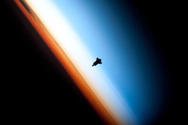 11. Силуэт шаттла Индевор на фоне Земли. Сфотографирован членами 22-й экспедиции на МКС. Оранжевый цвет — тропосфера, беловатый цвет — стратосфера (высота 8–16 км до 45–55 км), который переходит мезосферу (высота от 50–55 до 80 км). (Фото НАСА)