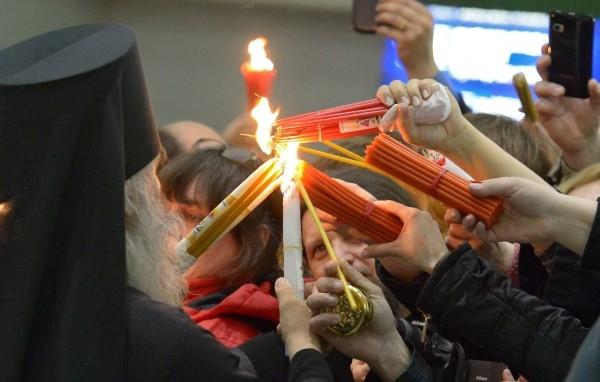 """Верующие зажигают свечи от Благодатного огня в аэропорту """"Внуково"""". Благодатный огонь доставлен спецрейсом из Иерусалима в Москву на праздничное пасхальное богослужение в храме Христа Спасителя."""