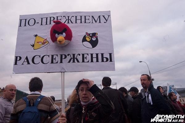 Участница акции с плакатом, на котором изображены птицы из популярной игры