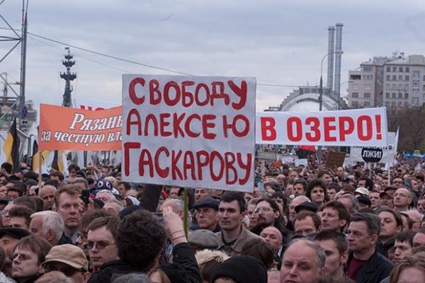 Участники акции держат в руках плакат в поддержку антифашиста Алексея Гаскарова. Он был задержан в конце апреля 2013 года по обвинению в участие в массовых беспорядках на Болотной площади в мае 2012 года.