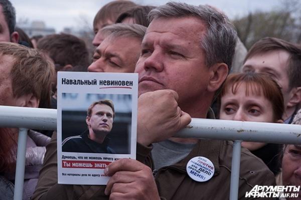 Участник митинга держит  листовку с фотографией оппозиционера Алексея Навального, который проходит по делу о хищениях лесоматериалов.
