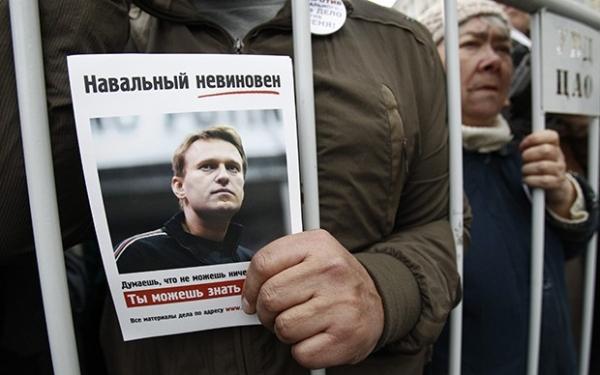 В руке у участника акции  листовка с фотографией оппозиционера Алексея Навального, который проходит по делу о хищениях лесоматериалов.