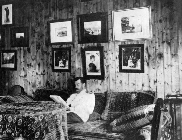Император Николай II сидит на диване в своей комнате в охотничьем домике и читает книгу. Репродукция. 1894