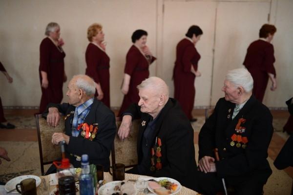 Ветераны Великой Отечественной войны Николай Пономарев, Владимир Архипенко и Николай Боженок (слева направо) смотрят на выступление хора на встрече ветеранских клубов города Болотное Новосибирской области.