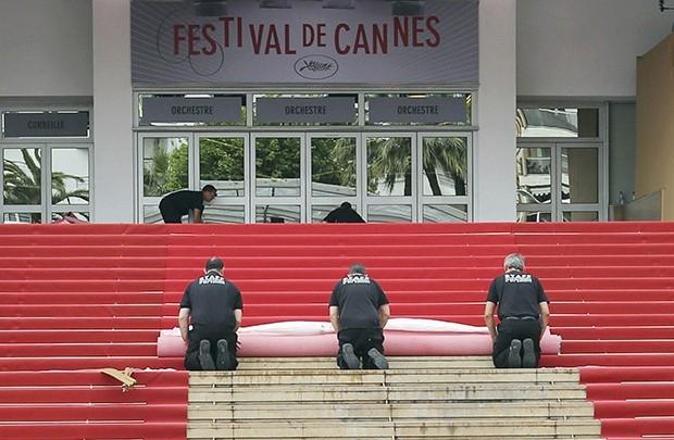 Рабочие расстилают красную ковровую дорожку перед началом церемонии
