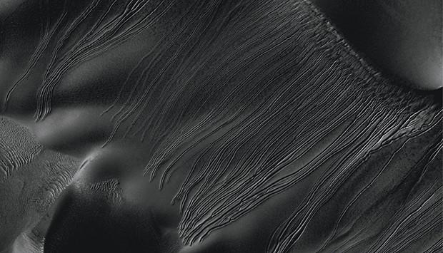 Специалисты NASA выяснили, что загадочные длинные овраги на Марсе, обнаруженные в ходе изучения снимков с автоматических зондов, являются следами от глыб замерзшей углекислоты или сухого льда, которые просто скатились вниз по марсианским дюнам. Это далеко