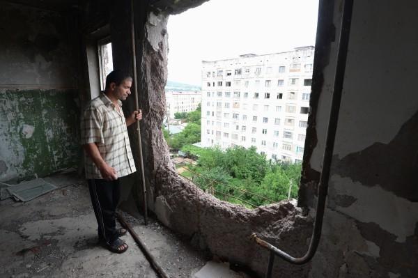2013 г.  Мужчина, живущий в девятиэтажном аварийном доме на улице Октябрьская в городе Цхинвал, смотрит через отверстие от танкового снаряда попавшего во время войны в соседнюю квартиру.