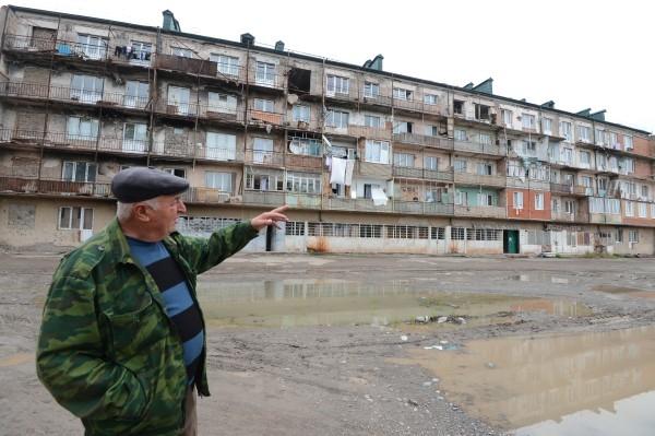 Житель города Цхинвал у аварийного пятиэтажного дома по улице Октябрьская. В доме остается много заселенных квартир. 2013
