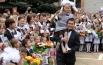 Старшеклассник несет на руках первоклассницу на торжественной линейке, посвященной началу нового учебного года, в гимназии города Казань.