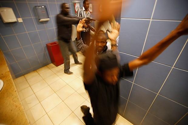 Полиция выводит освобождённых заложников из торгового центра.