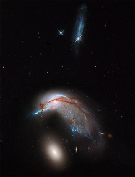 Столкновение галактик NGC 2936 и NGC 2937. Фотография сделана благодаря совмещению видимого и инфракрасного излучений камерой WFC3 на борту телескопа «Хаббл».