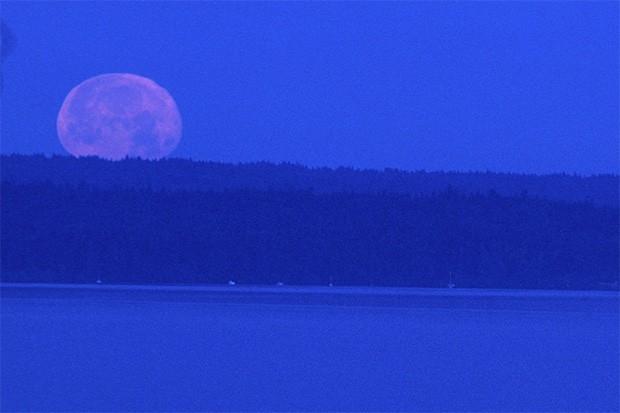 Луна во время заката над озером.