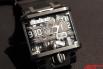 Эти часы показывают время не с помощью стрелок, а уникальным ленточным механизмом на котором располагаются цифры. Электро-механическая ременная передача двигает несколько ремней, выполненных из волокнистого нейлона со стеклянной матрицей.