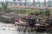 Рыбаки из уцелевших районов пытаются уберечь свои лодки, подняв их на сваях.