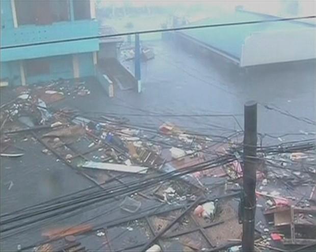 Потоки воды, подгоняемые сильным ветром, разносят обломки разрушенных зданий и прочий мусор.