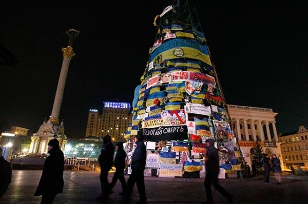 На Майдане Незалежности протестующие заклеили своими плакатами и листовками каркас новогодней ёлки, которую к моменту начала протестов собрать до конца власти не успели.