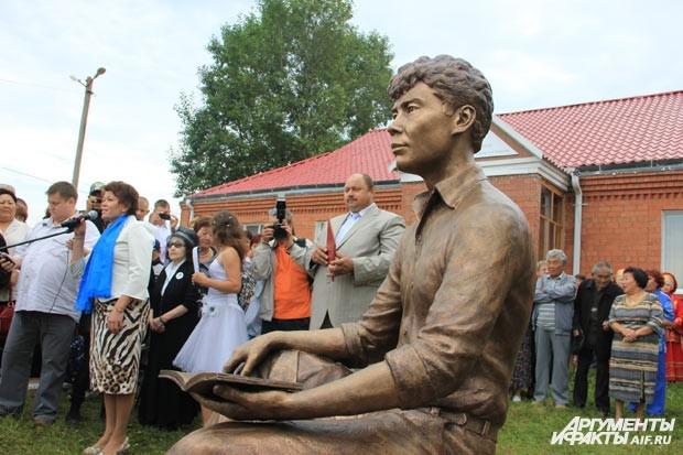 На невысоком постаменте Александр Вампилов представлен сидящим на пеньке с блокнотом и ручкой в руках.