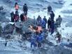 Столкнув пол-локомотива на берег Байкала, спасатели достают тело второго погибшего.