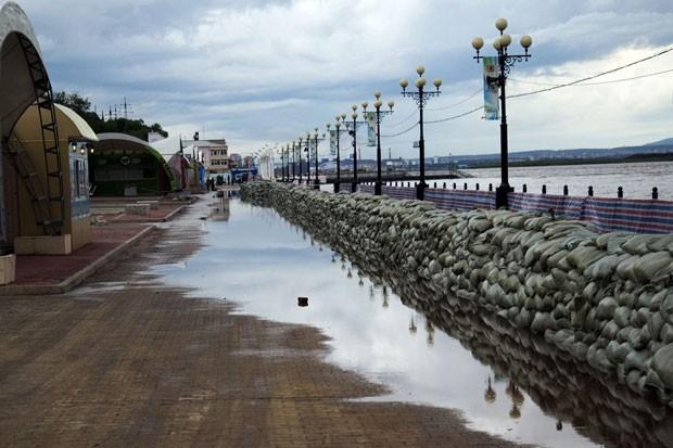 Вода пока не поднялась за мешками со стороны набережной, но видно, что заграждение пропускает даже то количество воды, которое переливается из русла.