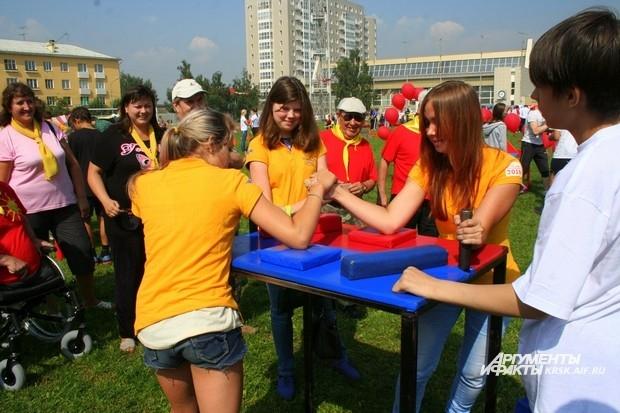 Участницы армрестлинга поддерживают спортсменок, соревнующихся в женском силовом экстриме. Женская солидарность.