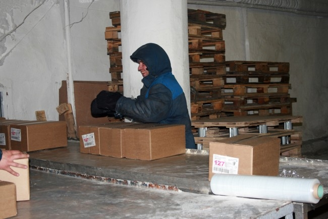 Днем и ночью здесь стоит 18-градусный холод. Но сортировщики замерзнуть не успевают - работа буквально сыплется сверху весь день