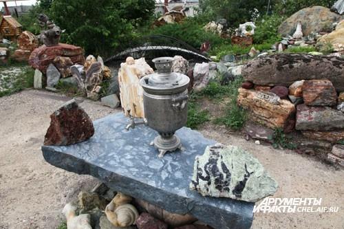 Для гостей накрыт каменный стол с самоваром.