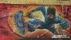 Бегущий прочь молодой парень в балаклаве и с  баллончиком краски, представлен на суд прохожих рядом рогатокопытным - во дворах жилых домов рядом с ЮУрГУ.