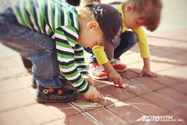 Детям раздали цветные мелки и разрешили рисовать на брусчатке перед зрителями.