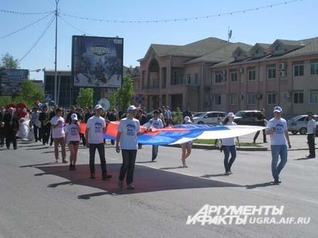 Впереди колонн активисты молодежных движений города несли государственный флаг.