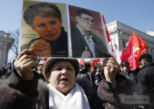 Участница митинга оппозиции держит портреты экс-премьер-министра Украины Юлии Тимошенко и экс-министра внутренних дел Украины Юрия Луценко