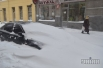 Прохожие идут возле занесенного снегом автомобиля на одной из улиц Львова