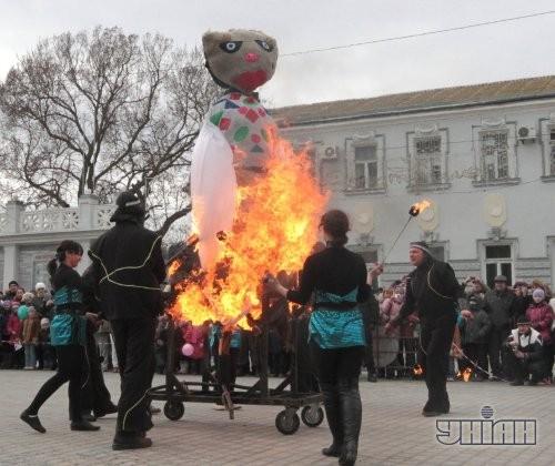 Участники празднования Масленицы сжигают чучело во время народных гуляний в Евпатории