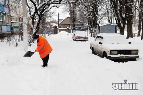 Сотрудница коммунальной службы отбрасывает снег в Одессе