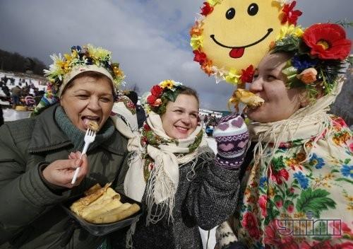 Участники празднования Масленицы едят блины во время народных гуляний в национальном музее архитектуры и быта Украины