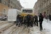 Люди толкают застрявшее на заснеженной дороге маршрутное такси на одной из улиц во Львове
