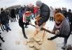 Участники празднования Масленицы распиливают бревно во время народных гуляний в национальном музее архитектуры и быта Украины