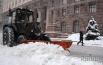Трактор чистит дорогу во время снегопада в Киеве