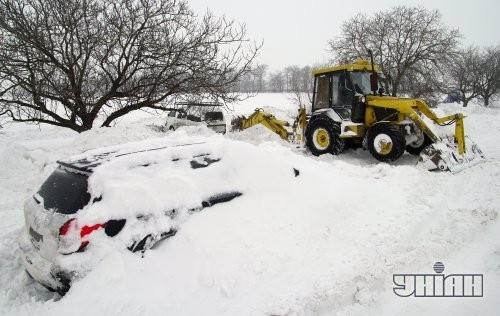 Трактор расчищает снег возле засыпанного снегом автомобиля на автотрассе Одесса – Ильичевск
