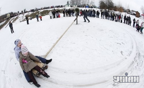 Дети катаются на санках во время народных гуляний в национальном музее архитектуры и быта Украины