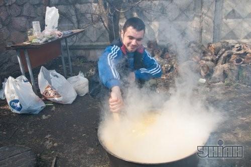 Мужчина готовит кулеш во время празднования Масленицы в Историко-культурном комплексе «Запорожский Дуб», в Запорожье