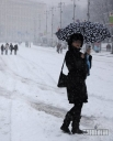 Девушка идет под зонтом во время снегопада в Киеве