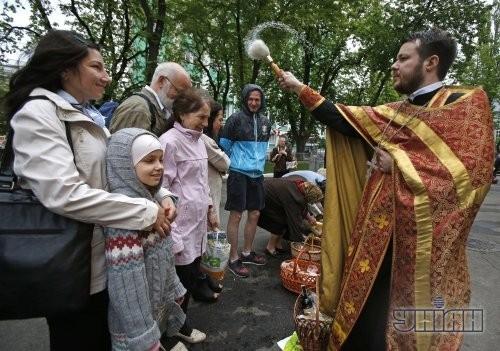 Священник освящает пасхальные корзины возле Владимирского собора в Киеве