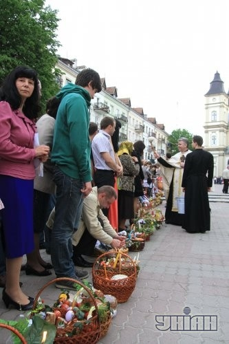Священник освящает пасхальные корзины накануне празднования Светлого Христова Воскресения возле Архикатедрального собора Воскресения УГКЦ в Ивано-Франковске